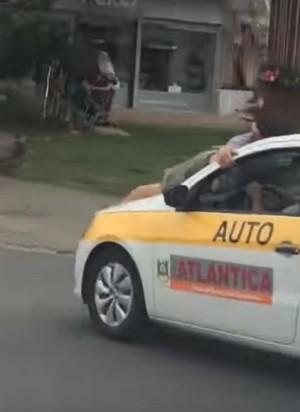 Vídeo mostra homem agarrado em capô de carro de autoescola (Foto: Reprodução/Youtube)
