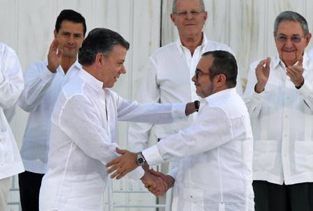 """En una ceremonia solemne, frente a 15 jefes de Estado y otros 2.500 invitados, el mandatario colombiano Juan Manuel Santos  y el líder rebelde Rodrigo Londoño (Timochenko), rubricaron con un """"balígrafo""""  el pacto de paz."""