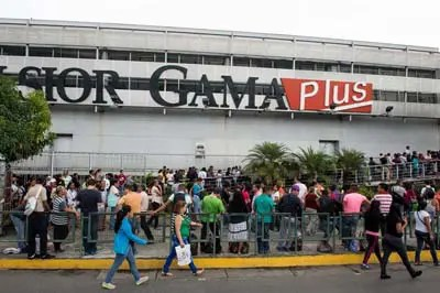 People queue up outside a supermarket in Caracas on January 13, 2015. Venezuela suffers a shortage of almost a third of commodities, inflation of 64% in 2014 and an economic recession caused in part by drought currency since 2013 is limiting essential imports. AFP PHOTO/FEDERICO PARRA