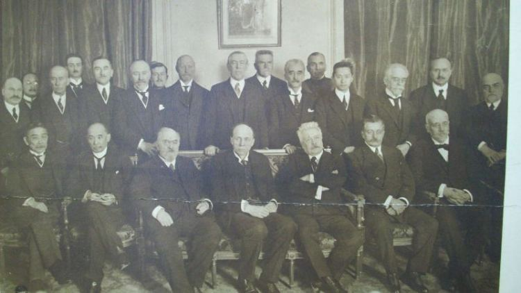 Photo of the members of the commission of the League of Nations created by the Plenary Session of the Preliminary Peace Conference, Paris, France 1919:   Standing (left to right): Constantine Diamandy (Rumania); Unidentified; Col. Edward M. House (United States); Unidentified; Roman Dmowski (Poland); Milenko R. Vesnitch (Serbia); Unidentified; Jan Smuts (British Empire); Woodrow Wilson (United States); Karal Kramar (Czechoslovakia); Paul Hymans (Belgium); V.K. Wellington Koo (China); Jaime Batalha-Reis (Portugal); Vittorio Scialoja (Italy); Unidentified   Seated (left to right): Sutemi Chinda (Japan); Nobuaki Makino (Japan); Leon Bourgeois (France); Robert Cecil (British Empire); Vittorio Emanuele Orlando (Italy); Epitacio Pessoa (Brazil); Eleftherios Venizelos (Greece)