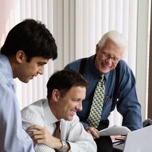 Three businessman looking at computer screen