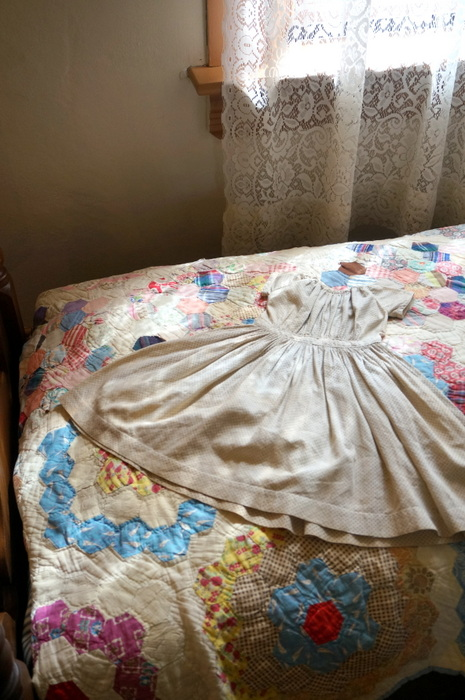 antique child's dress and quilt
