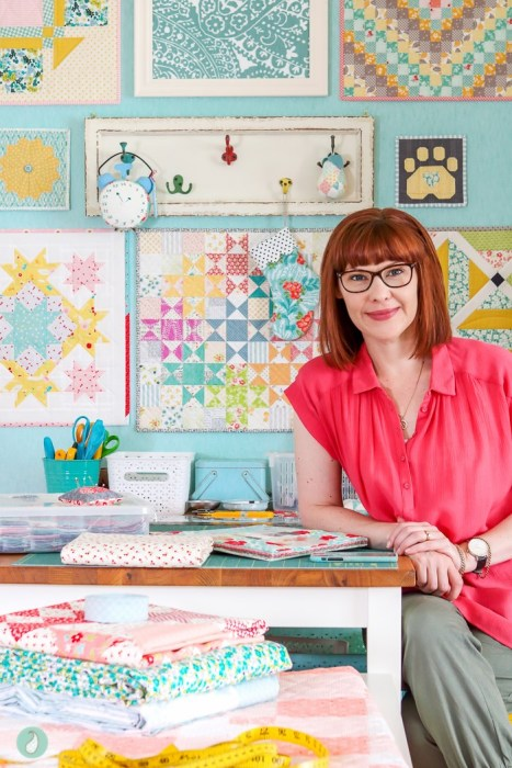 In Search of my Sewing Mojo and Other Tales of Summer by popular sewing blog, Diary of a Quilter: image of a woman sitting on a chair and leaning on a table that is covered with sewing supplies and quilting fabric.