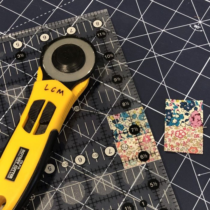 Scrappy Liberty Patchwork Pincushion by Guest May Chappell by popular quilting blog, Diary of a Quilter: image of a rotary cutter, cutting board, and Liberty Lawns fabric.