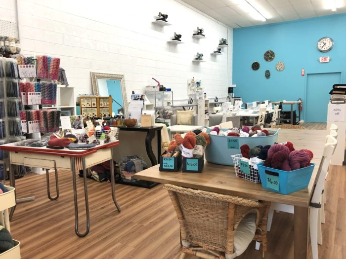Pintuck & Purl - Modern Fabric and Knitting Shop by popular quilting blog, Diary of a Quilter: image of baskets with balls of yarn inside, and sewing tables with sewing machines inside Pintuck and Purl.