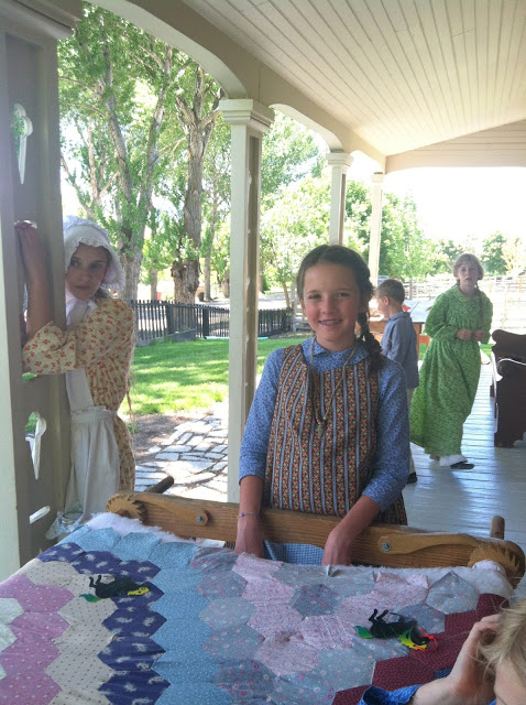 The Tale of a Pioneer Quilt, Cut in Two by popular quilting blog, Diary of a Quilter: image of girls outside on the front porch of house dresses in pioneer period clothing with a hexagon block quilt.