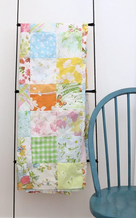 In Search of my Sewing Mojo and Other Tales of Summer by popular sewing blog, Diary of a Quilter: image of a pastel block quilt hanging on a decorative black ladder that's leaning against a wall.