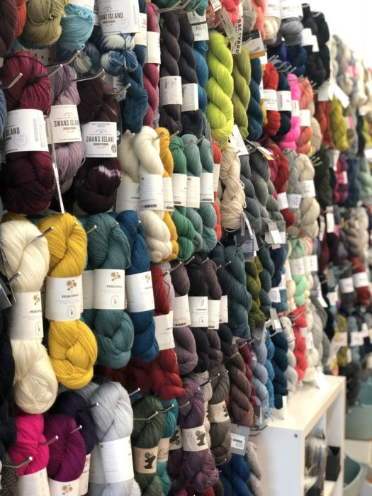 Pintuck & Purl - Modern Fabric and Knitting Shop by popular quilting blog, Diary of a Quilter: image of various colors of yarn hanging on display pegs inside Pintuck and Purl.