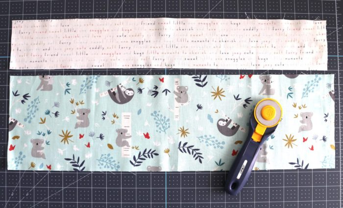 Bricks Baby Quilt Tutorial by popular quilting blog Diary of a Quilter: image of two strips of fabric on a cutting board with a rotary cutter lying on top.