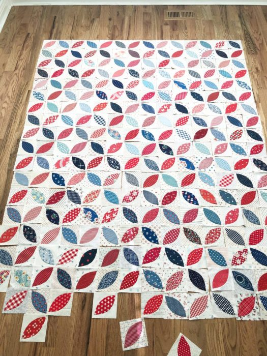 Red White and Blue orange peel applique quilt blocks by Amy Smart | More Orange Peel Applique Blocks + Real Life by popular Utah quilting blog: Diary of a Quilter: image of orange peel applique blocks laid out in a patter on a hard wood floor.