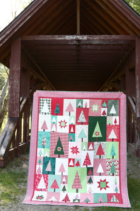 New Patchwork Forest Quilt Pattern: Pine Hollow Version by popular quilting blog, Diary of a Quilter: image of a red, white, and green patchwork forest tree quilt displayed outside in front of a covered bridge.