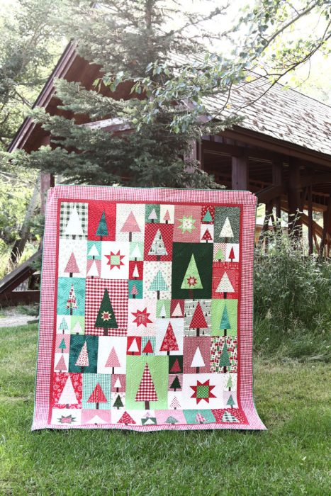 New Patchwork Forest Quilt Pattern: Pine Hollow Version by popular quilting blog, Diary of a Quilter: image of a red, white, and green patchwork forest tree quilt propped up outside against a pine tree.