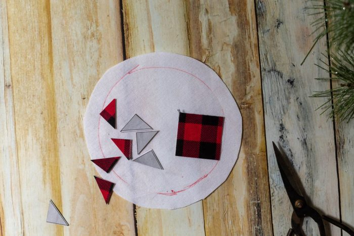 DIY Heirloom Christmas Ornament guest post by Coral + Co by popular Utah quilting blog, Diary of a Quilter: image of cut out piece of an Ohio star template on black and red plaid fabric.