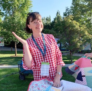A Year in Review: Looking back at 2019 + Looking forward to 2020 by popular Utah quilting blog: image of a woman sitting outside and holding a quilt on her lap.