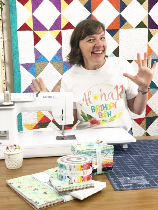 Birthday Bash at Missouri Star Quilt Company by popular quilting blog, Diary of a Quilter: image of woman standing next to a sewing machine inside the Missouri Star Quilt Company.