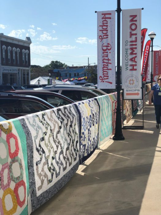 Birthday Bash at Missouri Star Quilt Company by popular quilting blog, Diary of a Quilter: image of quilts hanging outside of the Missouri Star Quilt company.