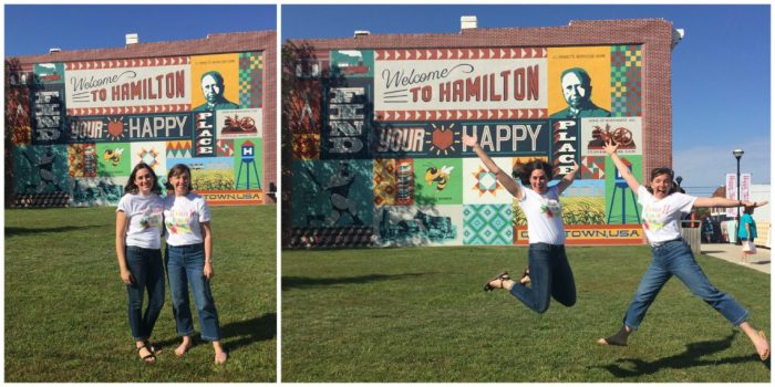 Birthday Bash at Missouri Star Quilt Company by popular quilting blog, Diary of a Quilter: image of two women jumping in front the Welcome to Hamilton sign.