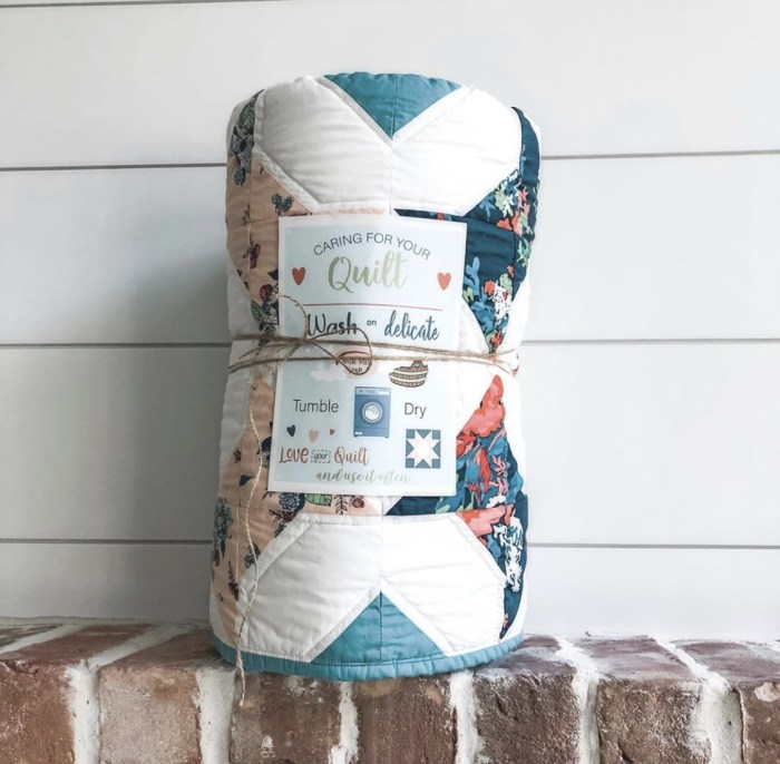 Free Printable Quilt Care Instructions + Gift Tags by popular Utah quilting blog, Diary of a Quilter: image of a rolled up quilt with a printable quilt care instructions card tied to it with twine.