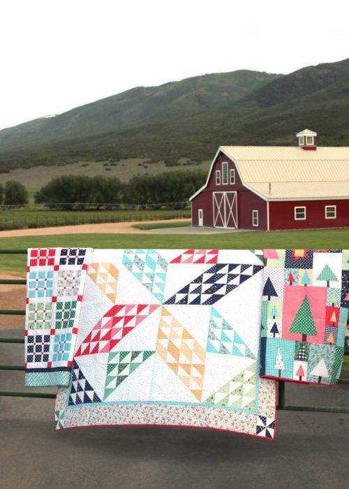 Sugarhouse Park Fabric Collection by Amy Smart by popular Utah quilting blog, Diary of a Quilter: image of quilts made out of Sugarhouse Park fabric draped over a fence outside in front of a barn.