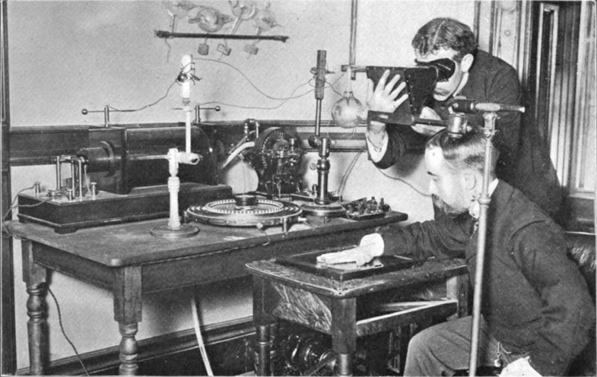 Photo of experimenters taking an X-ray with an early Crookes tub