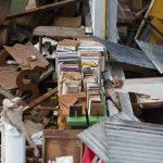 A single bookshelf remains standing amidst the debris.