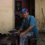 A shoeshine vendor in Santiago de Cuba the day before the hurricane , the ever-present photos of Che Guevara in the background.