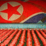 The Arrirang Games feature over 100,000 dancers, acrobats and other performers.  Here displaying the North Korean (DPRK) flag with a 'card trick', thousands of placards are held up to create massive scale images as a backdrop for the performers.