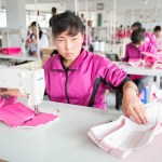 Garment Factory Work in Rasom. To circumvent the embargoes and sanctions placed on North Korea, Made in China labels are sewn in and retail hangtags attached for the boutique in Seoul which will be selling these booties.
