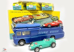 This is a superb example of the Corgi Gift Set No.16 Ecurie Ecosse Racing Car Transporter with 3 Racing Cars. The set contains No.1126 Car Transporter in dark metallic blue with a yellow interior. The sliding door and loading mechanism both work as they should. Inside you will find the vice on the workbench. It is in wonderful condition and most would say its in mint condition, it still has the track rod steering sticker applied to the front roof which is rarely present. As usual it comes with three racing cars, No.150S Vanwall Formula 1 Grand Prix Car in red, white driver and racing number 25, the self-adhesive wire spoke transfers have been applied. The 151A Lotus Mk.XI Le Mans Racing Car in blue with red seats and white driver, racing number 3 is also in excellent condition. Finally No.152S BRM Formula 1 Grand Prix Racing Car in green with the Union Flag to bonnet and racing number 1, again the wire spoke transfers have been applied. All have flat cast hubs, all are excellent plus to near Mint with excellent plus to near mint yellow and blue card boxes. The main box is in wonderful condition and one of the best I have seen for a very long time. It comes with the internal packing piece as well as the original gift set instructions. A very fine example of this sought after set.