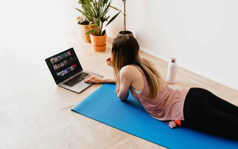 young woman lying on floor on mat while using laptop at home