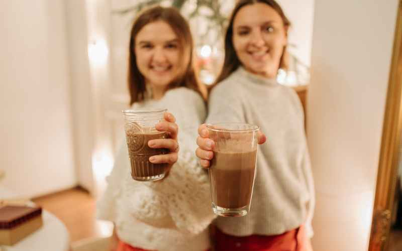 blur photo of two young girls holding glasses of chocolate drinks