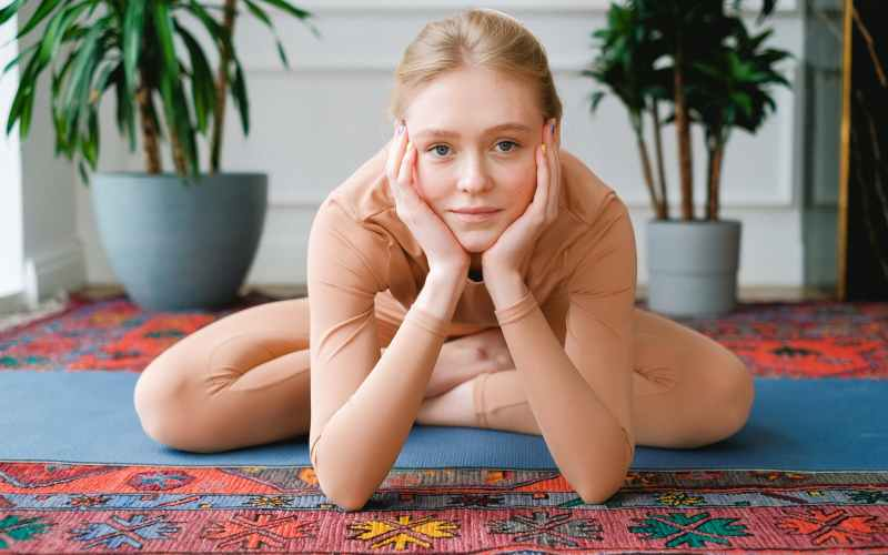 flexible woman sitting in lotus pose and leaning on hands