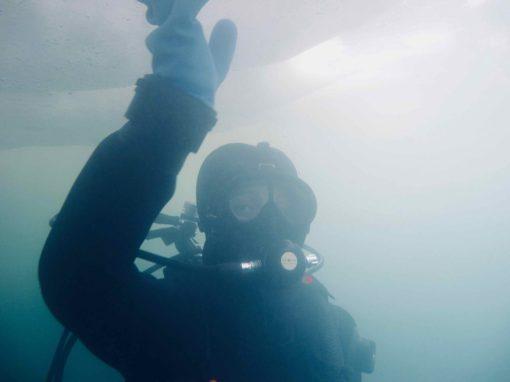 Plongeuse qui touche la glace au dessus d'elle
