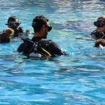 Un moniteur fait un briefing de plongée dans une piscine