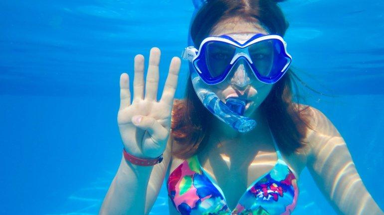 Une jeune plongeuse montre un quatre avec ses doigts