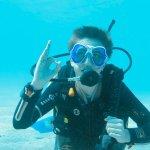 Un jeune plongeur fait le signe ok sous l'eau