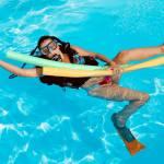 Une femme équipée pour plonger se tient à des boudins de piscine