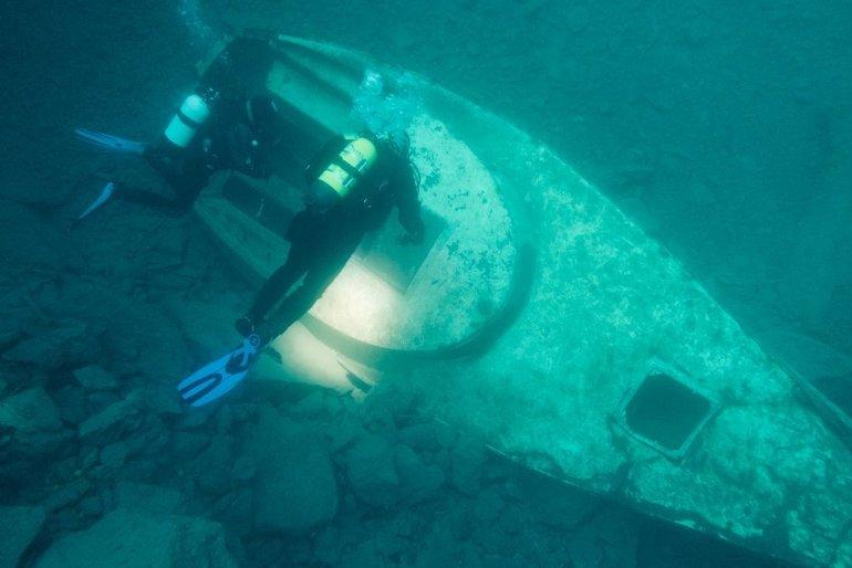 Deux plongeurs sur le petit voilier au fond de la carrière de Vodelée