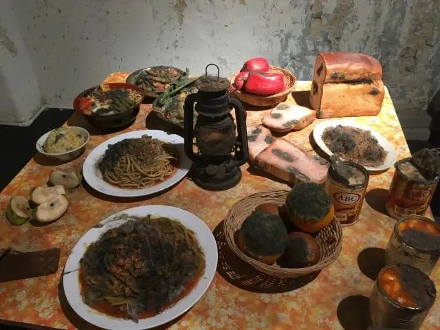 Table full of what looks like mouldy food including breadrolls, moodle dishes and canned goods. It's actually a model at Wonderfood Penang Malaysia