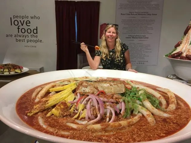Girl standing by a giant plastic model of a Curry Mee soup dish at Wonderfood Museum Penang