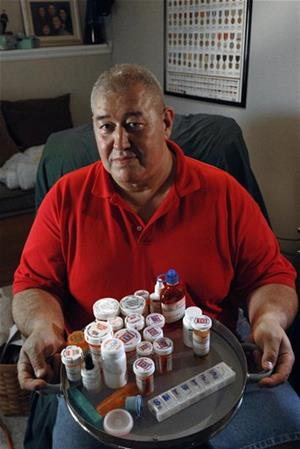 Retired U.S. Marine Staff Sgt. James Fernandez, 54, of Fredericksburg, Va., holds a tray containing some of the prescription medications he uses to overcome his severe pain, Wednesday, Aug. 8, 2007.   (AP Photo/Bob Martin)