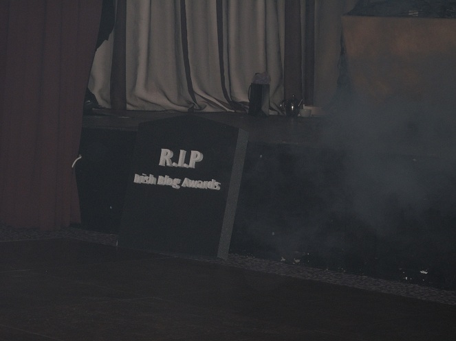 The Coffin is surrounded in fog generated by a smoke machine. the words written on the top of the coffin are: RIP IBA