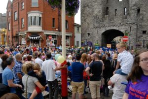 Shows the crowd in front of Laurence's gate enjoying a #MusicatTheGate event