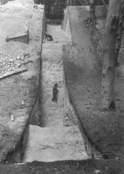 Image 02 - Section through the main ditch and rampart, 1969. The further figure kneels on the original ground surface.