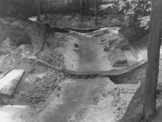 Image 07 - The east gate during excavation in 1970 looking into the fort. Part of the flint walling of the last entrance passage remains in position. The road retains some of the cobbles of its last phase of metalling. The post-holes of succesive gates can be seen on either side of the road in the vicinity of the figure and beyond.