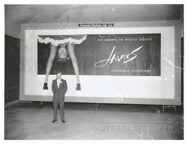 Gordon Hanes, of Hanes Corporation, in front of a Hanes Hosiery billboard, 1956.