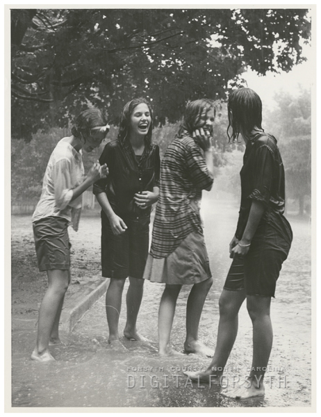 Mary Joe Petree, Louise Brock, Janie Hanes, and Martha Morefield are caught in the rain on Country Club Road, 1964.