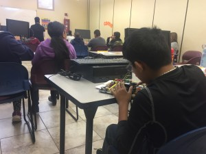 A student examines a motherboard in the back of class.