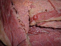 image of cooked slab of corned beef, partially sliced