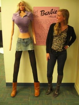 Girl standing next to a barbie with human dimensions